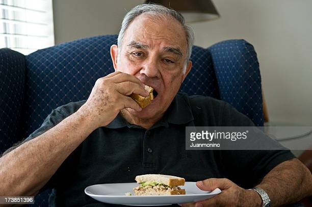 Senior hispanic having his sandwich