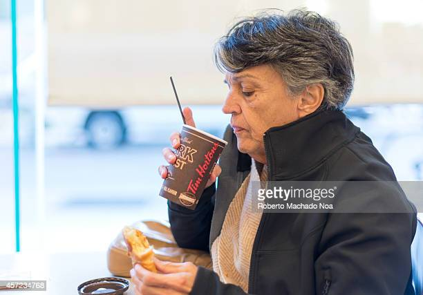 Senior Hispanic lady drinking Tim Horton's coffee in a shop close to chinatown
