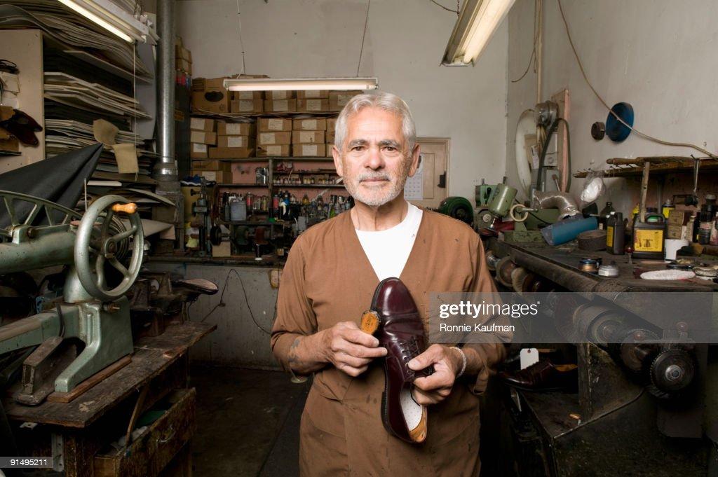 Senior Hispanic male cobbler holding shoe