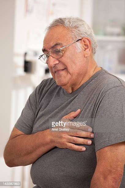 Senior Hispanic man clutching heart