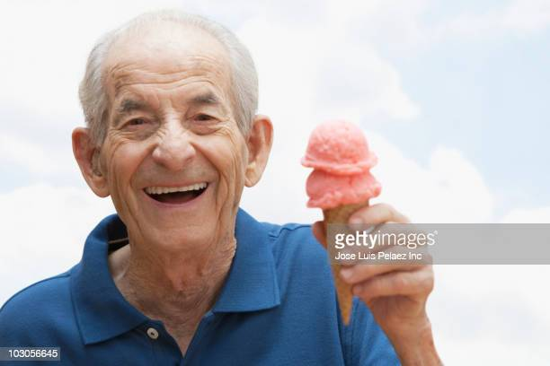 Senior Hispanic man holding ice cream cone