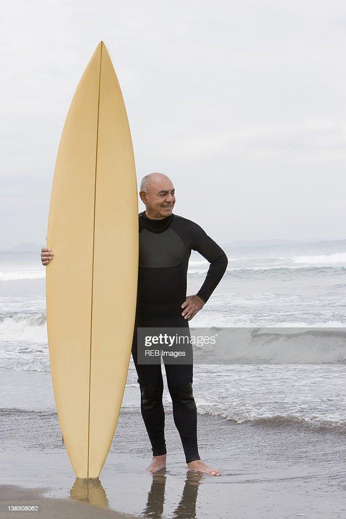 Senior Hispanic man holding surfboard on beach : Stock Photo