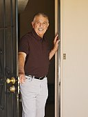Senior Hispanic man in open doorway