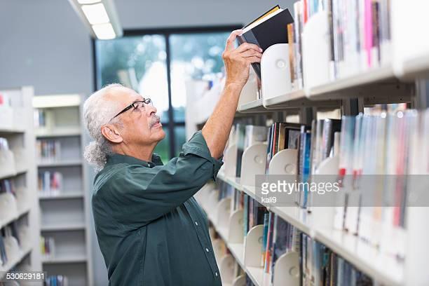 Homem Hispânico idosos na biblioteca