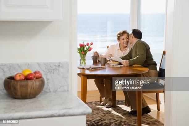 Senior Hispanic man kissing wife on cheek