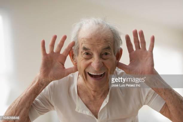 Senior Hispanic man making silly gesture