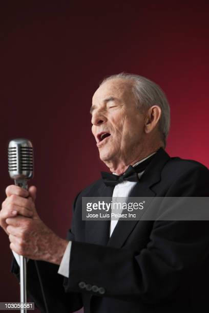 Senior Hispanic man singing into microphone