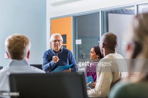 Senior Hispanic man teaching adult students