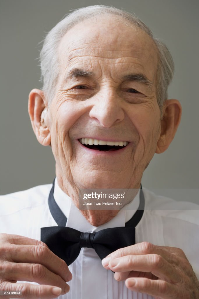 Senior Hispanic man tying bow tie : Stock Photo