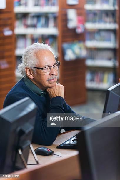 Homem Hispânico idoso usando um computador na biblioteca