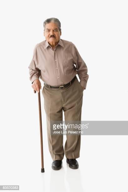 Senior Hispanic man walking with cane
