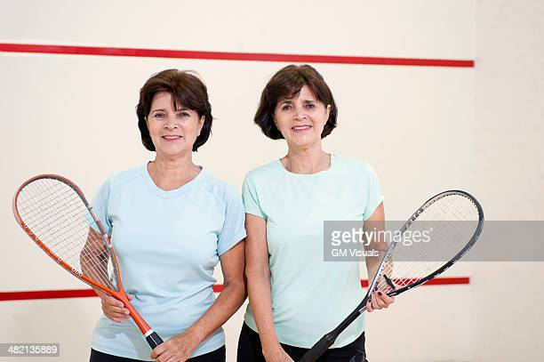 Senior Hispanic twins holding squash rackets