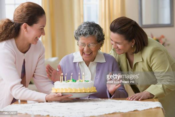 Senior Hispanic woman celebrating birthday with family