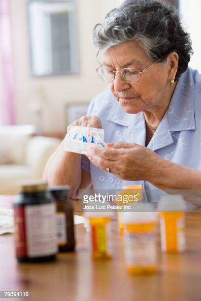 Senior Hispanic woman filing pill organizer