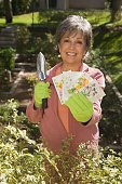 Senior Hispanic woman holding packets of flower seeds