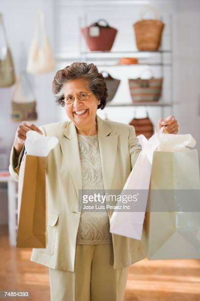 Senior Hispanic woman holding up shopping bags in boutique
