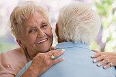 Senior Hispanic woman hugging husband