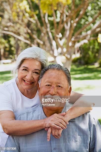 Senior hispanic woman hugging husband, portrait
