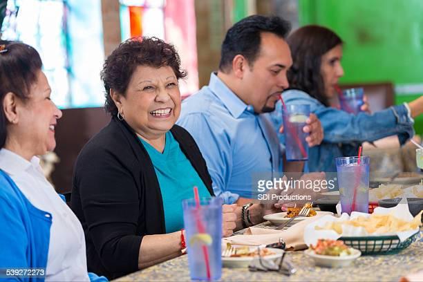 Senior femme hispanique multi-générationnelle au restaurant avec famille