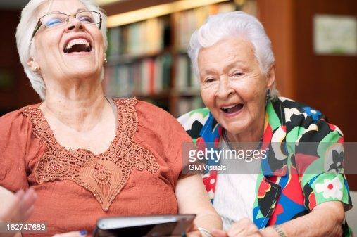 Senior Hispanic woman laughing and using digital tablet