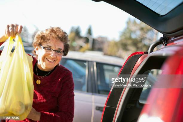 Senior Hispanic woman loading groceries in car