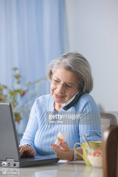 Senior Hispanic woman refilling drug prescription over the telephone