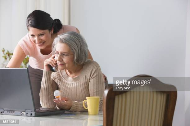 Senior Hispanic woman refilling drug prescription over the telephone