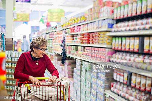 Senior Hispanic woman shopping in grocery store