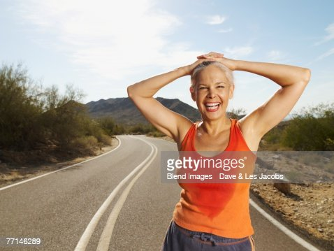 Senior Hispanic woman taking break from jogging