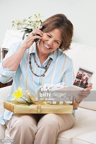 Senior Hispanic woman with gifts talking on cell phone