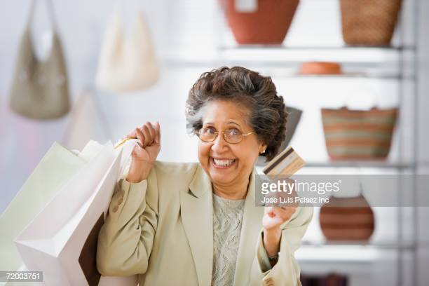 Senior Hispanic woman with shopping bags and credit card in boutique
