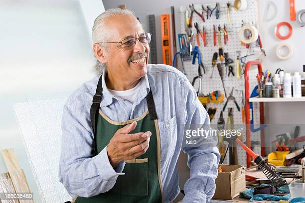 Senior Hispanic worker with tools in repair shop