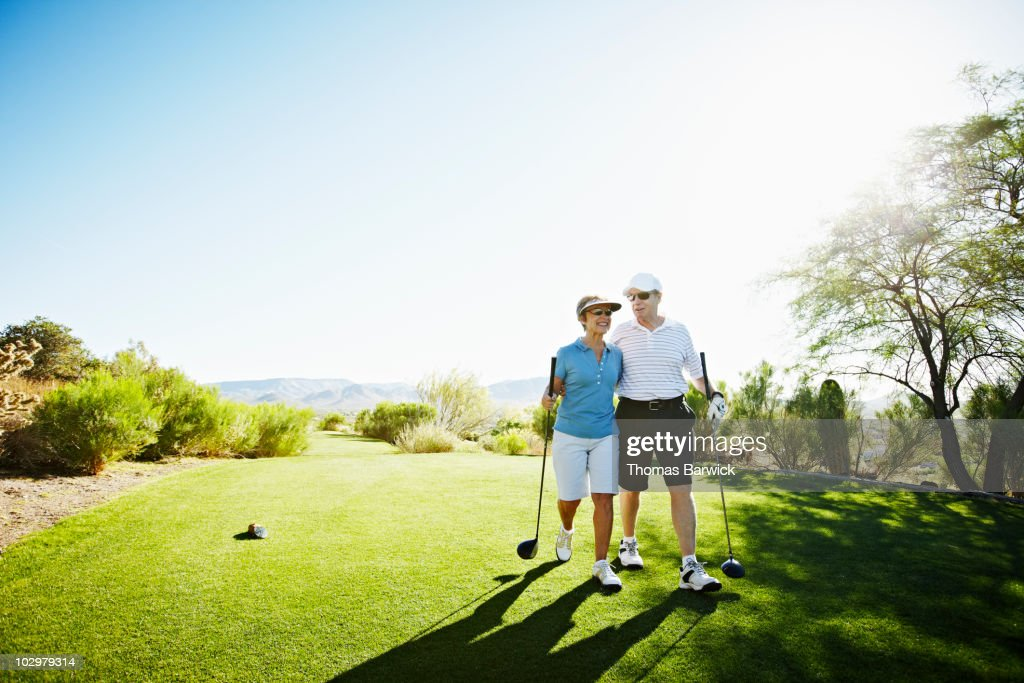 Senior husband and wife couple walking off tee : Stock Photo