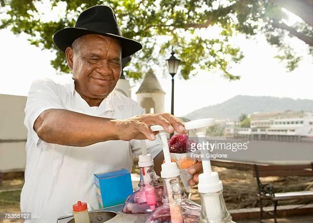 Senior ice cream vender making snow cone