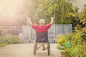 Back View of an older, handicapped man, arms and crutches raised in happiness, sunflare