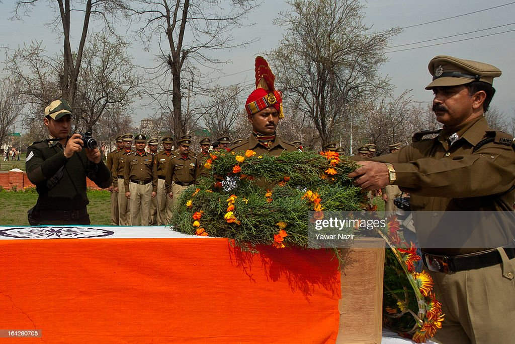 A senior Indian Border Security Force (BSF) officer lays a wreath on the coffin containing the body of his killed comrade, Krishna Kalita, on March 22, 2013 in Srinagar, the summer capital of Indian administered Kashmir, India. A wreath-laying ceremony was held by the BSF for their killed comrade after suspected rebels shot him dead yesterday and wounded two others when they fired on their vehicle on a highway. Kashmir valley is on the alert since the hanging of Afzal Guru, a local resident who was convicted of carrying out a deadly attack on the Indian Parliament in 2001.