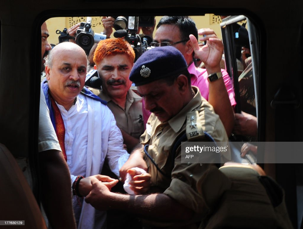 Senior Indian VHP leader, Praveen Togadiya (L), is arrested by policemen during an attempted procession in Ayodhya on August 25, 2013. Indian police arrested leaders of a Hindu forum to try and prevent a march to a pilgrimage town where the 1992 razing of a mosque sparked deadly sectarian riots. Organisers from the Vishwa Hindu Parishad (VHP, World Hindu Council) and the Press Trust of India (PTI) said some 125 people were detained in the northern state of Uttar Pdaesh.