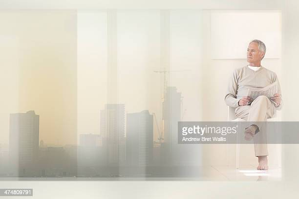 Senior investor relaxing in city apartment