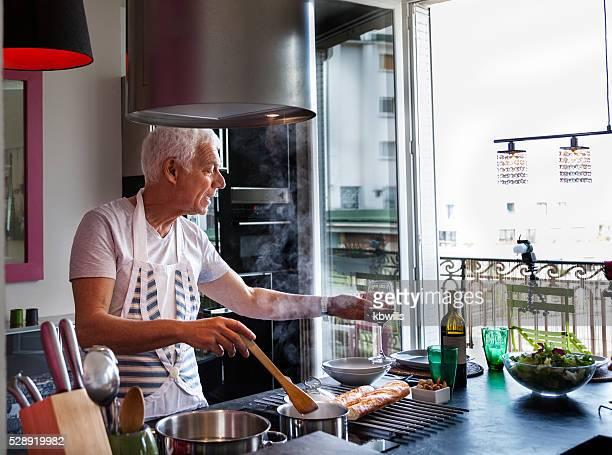 Senior italienische Mann kocht Mahlzeit, Getränke und Wein moderne Wohnung
