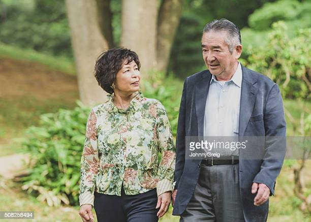 Senior Japanese couple walking together in the park