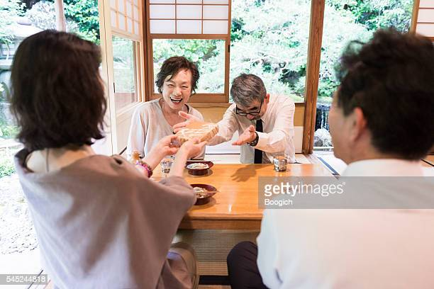 Senior Japanese Friends Give Gift in Restaurant Kyoto Japan