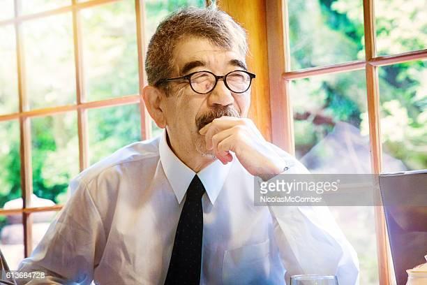 Senior Japanese man hiding smile during conversation
