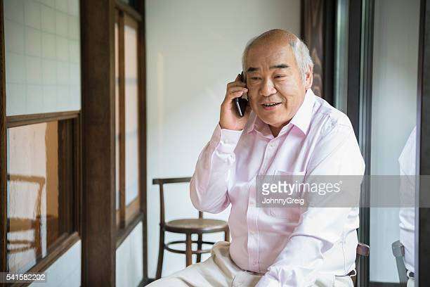 Senior Japanese man on telephone