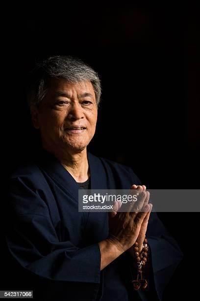 Senior Japanese man praying at a temple