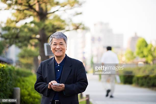 Senior japanische Mann mit einem Smartphone