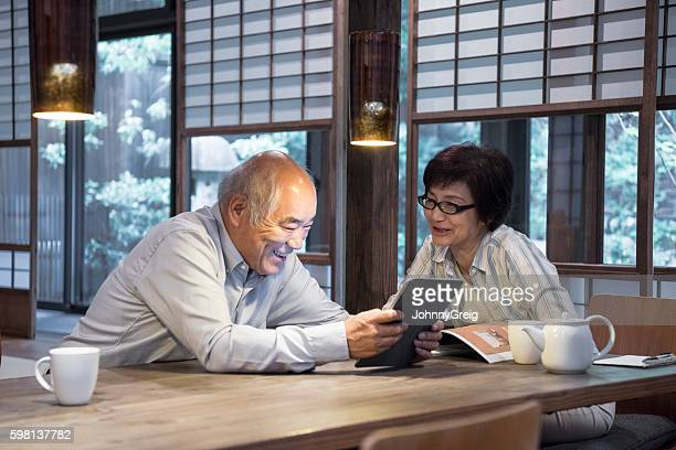 Senior Japanese man using digital tablet with woman