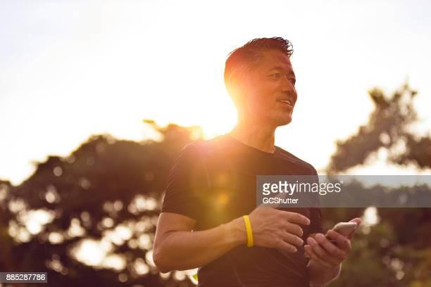 日没時に彼のスマート フォンで年配の日本人男性