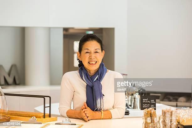 Senior Japanische Frau Begrüßung der Kunden im Café