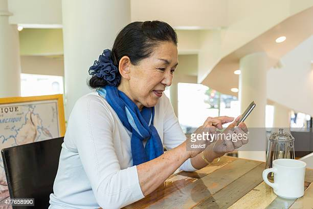 Senior Japanische Frau mit Handy in ein Café