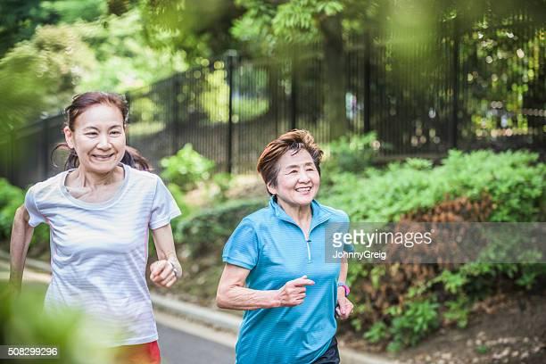 高齢者の女性のためにジョギングを一緒に、笑顔